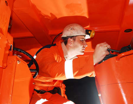 Miner operating heavy machinery in a mine shaft stock photo photo