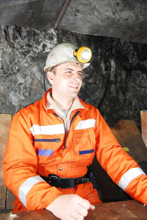 Smiling miner in a mine shaft having a break stock photo Imagens