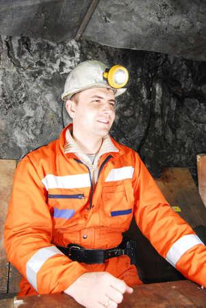 Sonriente minero en una mina de eje con una pausa de foto