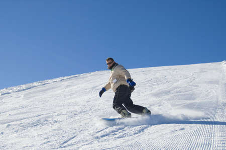 Snowboarder on a mountain in a clear blue sunshine day stock photo