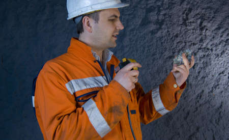 Engineer inspecting mineral with flashlight stock photo