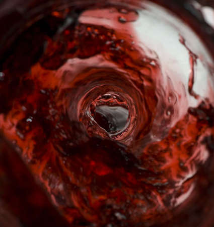 Wine pouring in a glass captured from unusual POV inside the bottle stock photo Imagens