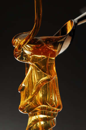 Golden honey dripping from a spoon  Imagens
