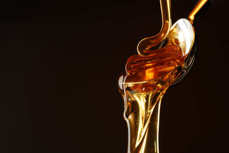 liquid gold: Honey flowing out of the spoon Stock Photo