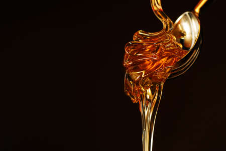 Honey with gold color isolated on black  Stock Photo