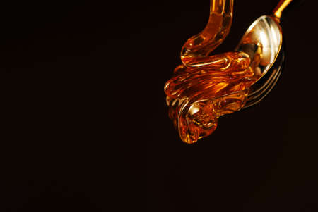 Honey drop with gold color isolated on black stock photo Stock Photo