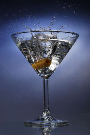Cocktail splash with an olive on blue background