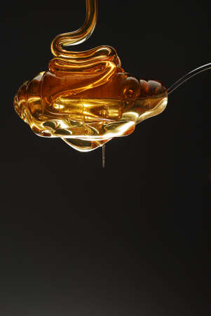 Golden honey being poured on spoon stock photo