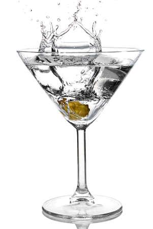 Olive splash into cocktail on white background photo