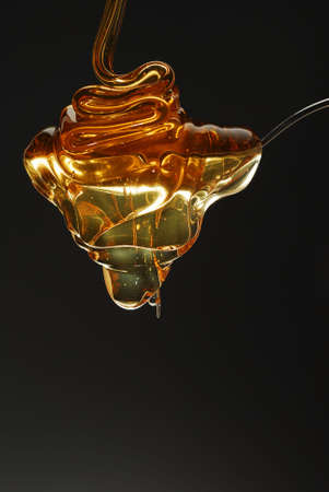 Golden honey spilling over the spoon stock photo