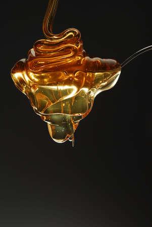 Golden honey spilling over the spoon stock photo