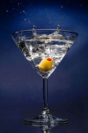 Cocktail with an olive splash on blue background