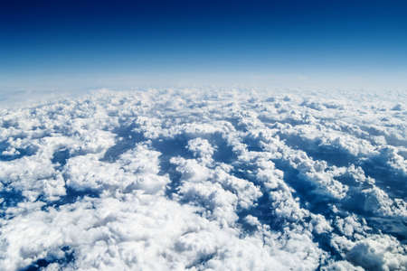 View from airplane window over the clouds