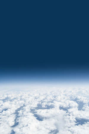 View at earth from airplane window above the clouds