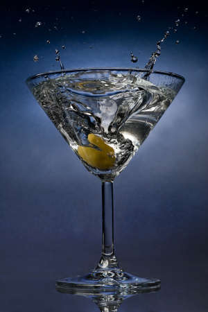 Martini cocktail splash with an olive close view