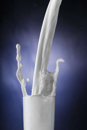 Morning start concept - milk splashing in a glass Stock Photo