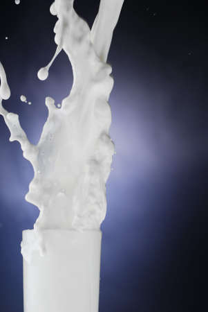 Milk coming out of the glass as it is being poured Stock Photo