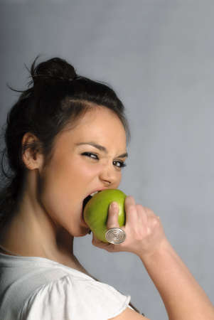 Beautiful young woman biting an apple portrait isolated photo