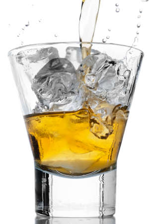 Pouring whiskey on the rocks in a glass Stock Photo