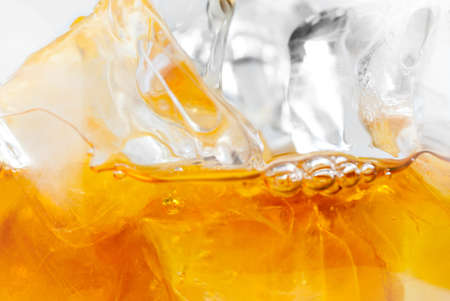 Extreme closeup of Whiskey with ice cubes isolated on white Stock Photo
