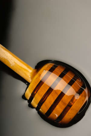 sweeten: Wooden dipper in very smooth golden honey  Stock Photo