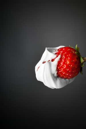 cremoso: Una fresa sumergida en crema de yogur puro blanco aislado en gris Foto de archivo