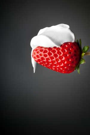 Dessert cream youghurt over red strawberry isolated on gray side lighting Stock Photo