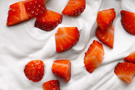 Chopped strawberry in a bowl of whipped cream