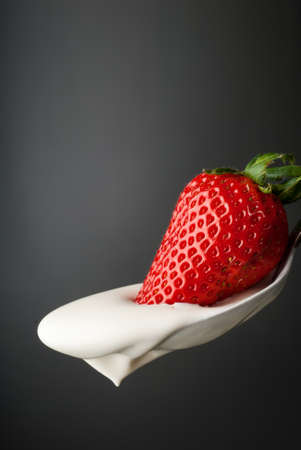 Whipped cream and a fresh strawberry in a silver spoon isolated on gray photo