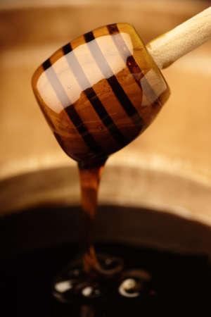 Smooth dripping honey from a wooden dipper Standard-Bild