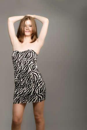 Girl model with zebra dress isolated on gray