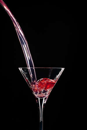 Pouring a red spirit in a Martini glass on black