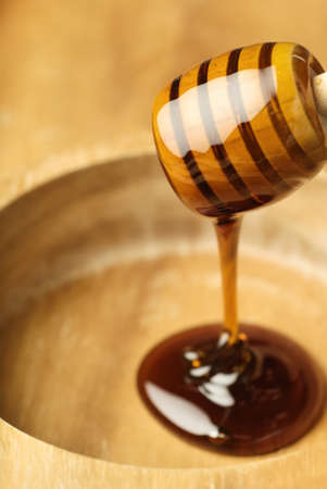 sweeten: Wooden dipper covered with light golden honey