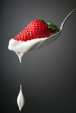 Dripping cream in air from a silver spoon isolated on gray