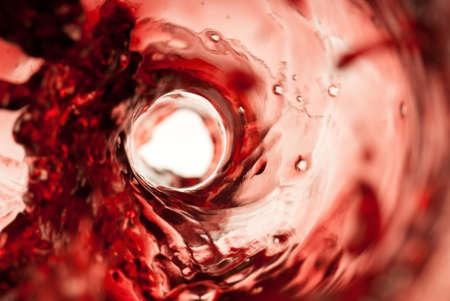 Dark red wine splashing inside a glass bottle