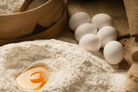 tilt shift: Egg yolk closeup in a heap of white flour