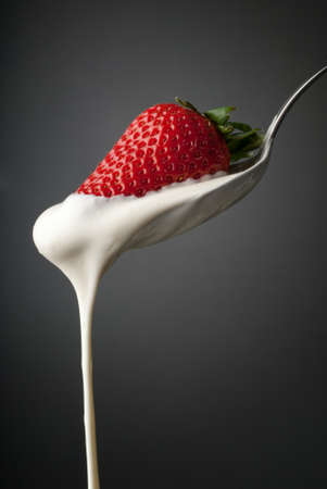 Dripping cream on a silver spoon and a strawberry
