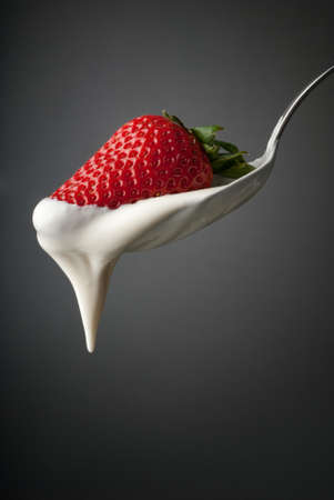 Silver spoon with a strawberry and cream Stock Photo - 13378473