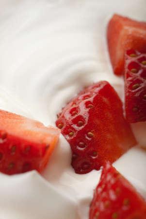 Whipped cream engulfing red chopped strawberries