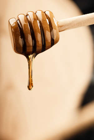 Dripping light honey from a wooden dripper