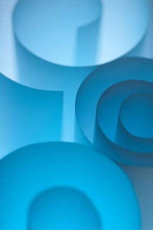Blue paper rolls under soft light in studio photo