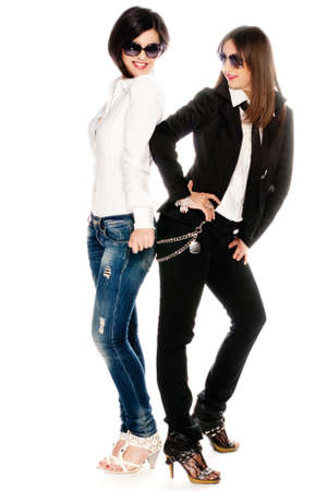 Two young adult girls dressed up in a white studio photo