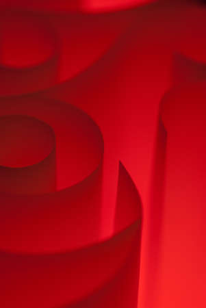 Red spirals of paper closeup lit in studio photo