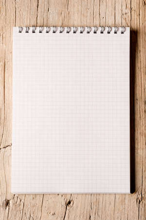 Blank white notepad on a hardwood floor lit on the side photo