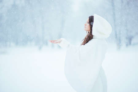 Girl alone in the snow, enjoying the tranquility and quietness of the snowfall