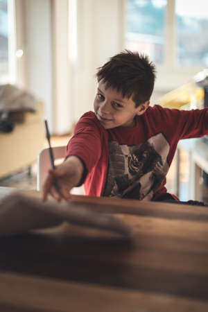 Boy cheering that the homework is finished by throwing the notebook