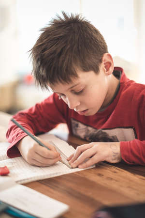 Young boy doing homework from mathematics at home