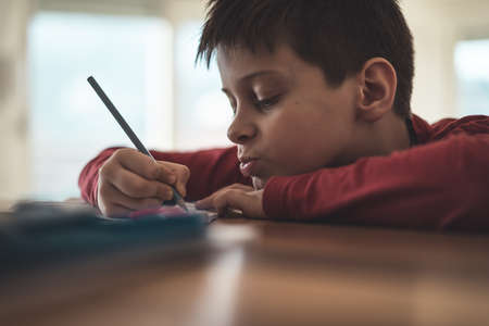 Boy writing homework reluctantly at home