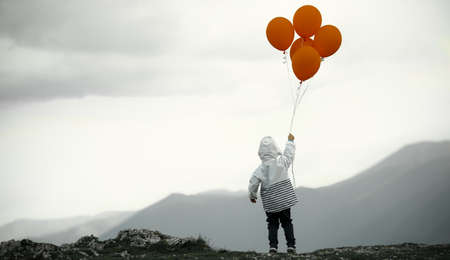 Small boy with balloons on top of mountain