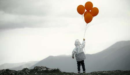 Kleiner Junge mit Ballons auf dem Berg